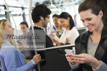New York City park. People, men and women on a city bus. Public transport. Keeping in touch. A young woman checking or using her cell phone. Stock Photo - Premium Royalty-Free, Image code: 6118-07354346