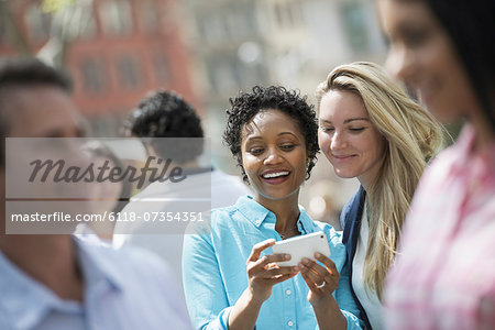 People outdoors in the city in spring time. New York City. A group of men and women, two women looking at a cell phone. Stock Photo - Premium Royalty-Free, Image code: 6118-07354351