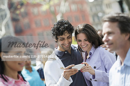 People outdoors in the city in spring time. New York City. A group of men and women, a couple at the centre looking at a cell phone. Stock Photo - Premium Royalty-Free, Image code: 6118-07354352