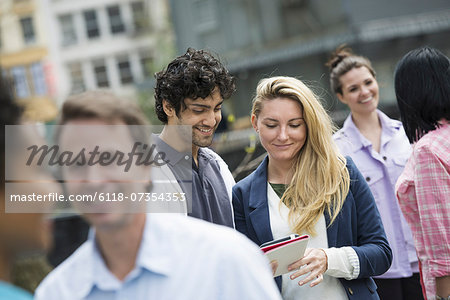 People outdoors in the city in spring time. New York City. A group of men and women, a couple at the centre looking at a cell phone. Stock Photo - Premium Royalty-Free, Image code: 6118-07354353