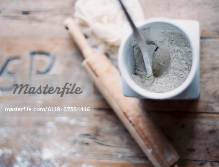 A domestic kitchen. A small group of objects. A rolling pin and jar of flour on a worn tabletop. View from above. Stock Photo - Premium Royalty-Free, Image code: 6118-07354418