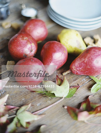 A domestic kitchen tabletop. A small group of fresh organic pears and a stack of white plates. Stock Photo - Premium Royalty-Free, Image code: 6118-07354433
