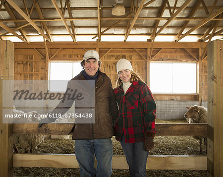 An Organic Farm in Winter in Cold Spring, New York State. A farmer and a woman standing by a pen full of sheep. Stock Photo - Premium Royalty-Free, Image code: 6118-07354438