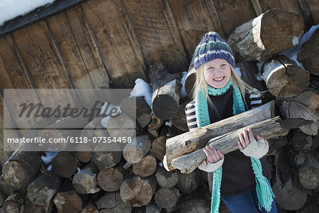 Winter scenery with snow on the ground. A girl collecting firewood from the log pile. Stock Photo - Premium Royalty-Free, Image code: 6118-07354458