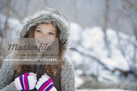 Winter scenery with snow on the ground. A young girl in a woolly hat with ski gloves on. Stock Photo - Premium Royalty-Free, Image code: 6118-07354469