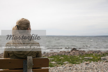 A woman with long blonde hair wearing a brown hooded coat, seated on a bench looking out to sea. Stock Photo - Premium Royalty-Free, Image code: 6118-07354482