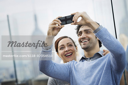New York City. An observation deck overlooking the Empire State Building. A young couple taking photographs with a mobile phone. Stock Photo - Premium Royalty-Free, Image code: 6118-07354510