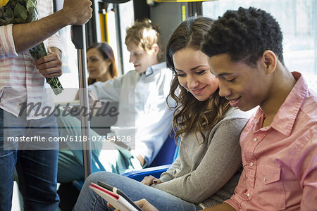 Urban Lifestyle. A group of people, men and women on a city bus, in New York city. A couple side by side looking at a digital tablet. Stock Photo - Premium Royalty-Free, Image code: 6118-07354528