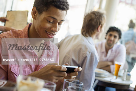 Urban Lifestyle. Three young men in a cafe. One checking his smart phone. Two talking at a table. Stock Photo - Premium Royalty-Free, Image code: 6118-07354531