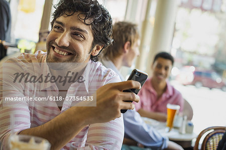 Urban Lifestyle. Three young men around a table in a cafe. One using his smart phone Stock Photo - Premium Royalty-Free, Image code: 6118-07354533