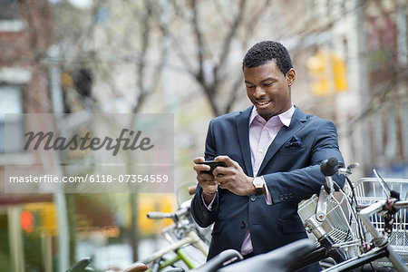 City life in spring. A young man in a blue suit, by a bicycle park. Checking his smart phone for messages. Stock Photo - Premium Royalty-Free, Image code: 6118-07354559