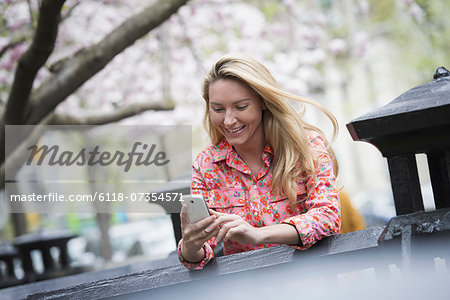 City life in spring. A young woman with long blonde hair sitting in a city park, looking at her smart phone. Stock Photo - Premium Royalty-Free, Image code: 6118-07354571