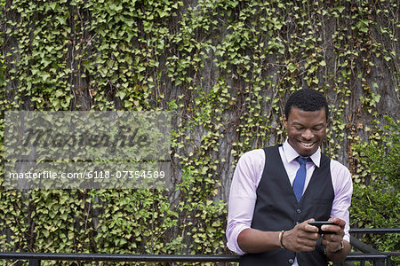 City life in spring. City park with a wall covered in climbing plants and ivy.  A young man in a waistcoat, shirt and tie checking his phone. Stock Photo - Premium Royalty-Free, Image code: 6118-07354589
