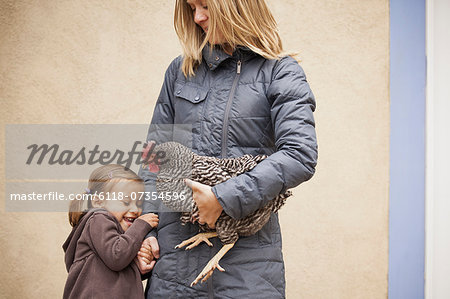 A woman in a grey coat holding a black and white chicken with a red coxcomb under one arm. A young girl beside her holding her other hand Stock Photo - Premium Royalty-Free, Image code: 6118-07354596