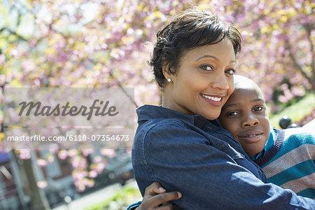 A New York city park in the spring. Sunshine and cherry blossom. A mother and son spending time together. Stock Photo - Premium Royalty-Free, Image code: 6118-07354673