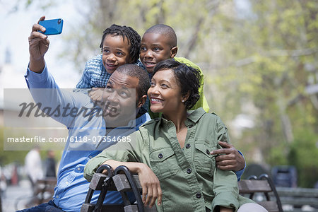 A New York city park in the spring. A family, parents and two boys taking a photograph with a smart phone. Stock Photo - Premium Royalty-Free, Image code: 6118-07354685