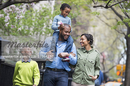 A New York city park in the spring. A family, parents and two boys.  A child riding on his father's shoulders. Stock Photo - Premium Royalty-Free, Image code: 6118-07354697