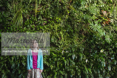 Outdoors in the city in spring. An urban lifestyle. A young girl standing in front of a wall covered with ferns and climbing plants. Stock Photo - Premium Royalty-Free, Image code: 6118-07354753