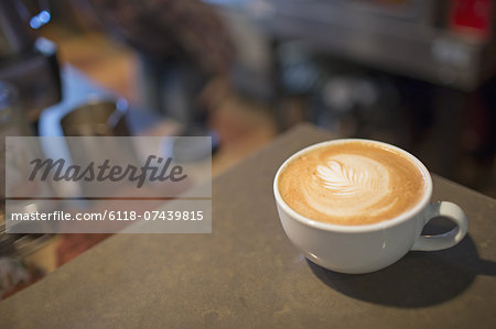 Coffee shop table. A full white china cup of coffee with a frothed milk top. Stock Photo - Premium Royalty-Free, Image code: 6118-07439815