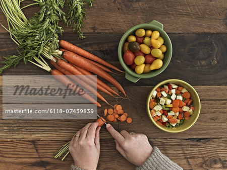 A person preparing fresh vegetables on a wooden table. Stock Photo - Premium Royalty-Free, Image code: 6118-07439839