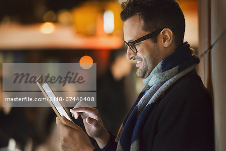 A man in a city at night, looking at a computer tablet. Stock Photo - Premium Royalty-Free, Image code: 6118-07440408