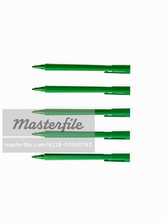 Office supplies. Green coloured pens, felt nibs and pen top cases, arranged in a row. Stock Photo - Premium Royalty-Free, Image code: 6118-07440743