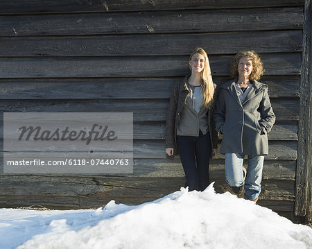 A mother and daughter standing leaning against the wooden wall of a barn on a farm. Snow piled up at their feet. Stock Photo - Premium Royalty-Free, Image code: 6118-07440763