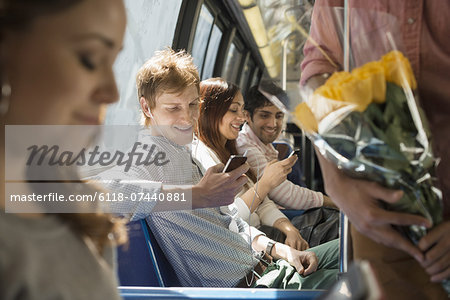 Urban Lifestyle. A group of people, men and women on a city bus, in New York city. Two people checking their smart phones. Stock Photo - Premium Royalty-Free, Image code: 6118-07440881