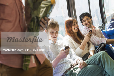 Urban Lifestyle. A group of people, men and women on a city bus, in New York city. Two people checking their phones. One man standing holding a bunch of flowers. Stock Photo - Premium Royalty-Free, Image code: 6118-07440882