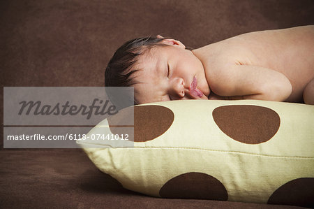 A newborn baby with his head turned to one side, lying sleeping on a polka dotted pillow. Stock Photo - Premium Royalty-Free, Image code: 6118-07441012