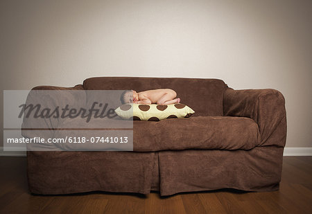A naked newborn baby lying on his front, sleeping on a pillow on a brown couch. Stock Photo - Premium Royalty-Free, Image code: 6118-07441013