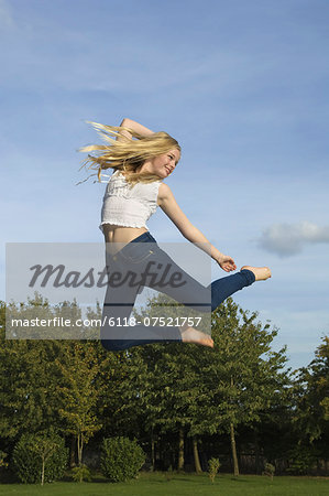 Teenage girl with long blond hair jumping in the air. Stock Photo - Premium Royalty-Free, Image code: 6118-07521757