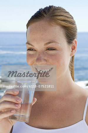 A spa treatment centre. A young woman drinking a glass of water. Stock Photo - Premium Royalty-Free, Image code: 6118-07521811