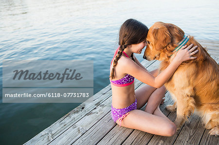 A young girl and a golden retriever dog sitting on a jetty. Stock Photo - Premium Royalty-Free, Image code: 6118-07731783