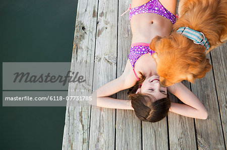 A young girl and a golden retriever dog on a jetty. Stock Photo - Premium Royalty-Free, Image code: 6118-07731785