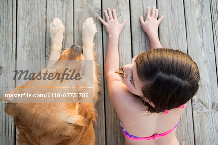 A young girl and a golden retriever dog side by side on a jetty. Stock Photo - Premium Royalty-Free, Image code: 6118-07731786
