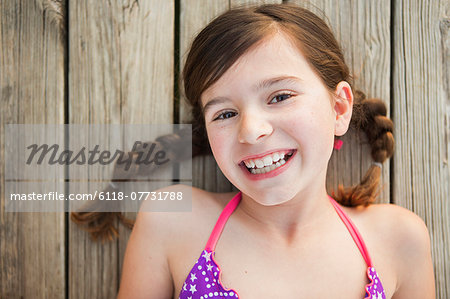 A young girl lying on a jetty looking upwards. Stock Photo - Premium Royalty-Free, Image code: 6118-07731788