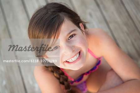 A young girl seated on a jetty looking upwards. Stock Photo - Premium Royalty-Free, Image code: 6118-07731789