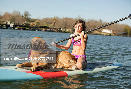 A child and a retriever dog on a paddleboard on the water. Stock Photo - Premium Royalty-Free, Image code: 6118-07731793