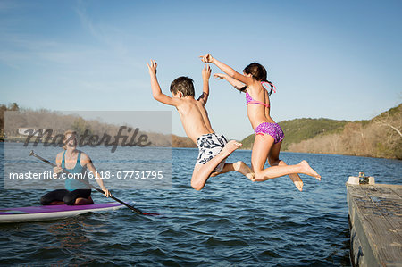 Two children leaping into the water from a jetty. Stock Photo - Premium Royalty-Free, Image code: 6118-07731795