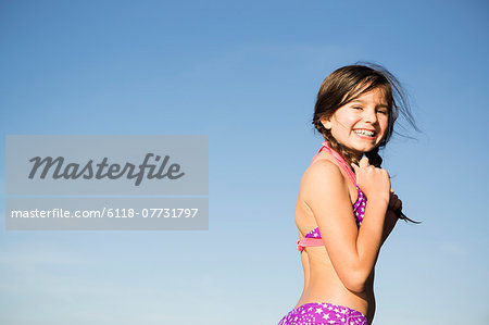 A young child in a bikini with plaited hair. Stock Photo - Premium Royalty-Free, Image code: 6118-07731797