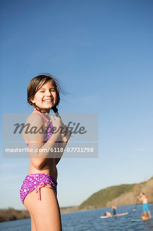 A young girl on a jetty with paddleboarders in the background. Stock Photo - Premium Royalty-Free, Image code: 6118-07731798