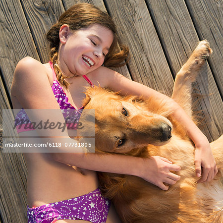 A girl in a bikini lying beside a golden retriever dog, viewed from above. Stock Photo - Premium Royalty-Free, Image code: 6118-07731805
