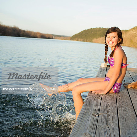 A girl in a bikini sitting on a jetty with her feet in the water. Stock Photo - Premium Royalty-Free, Image code: 6118-07731806