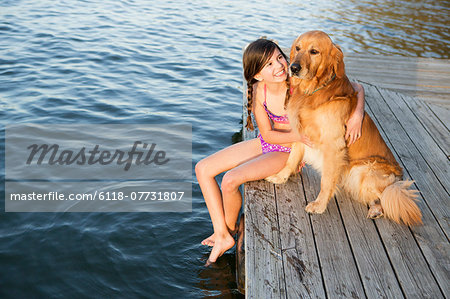 A girl and her golden retriever dog seated on a jetty by a lake. Stock Photo - Premium Royalty-Free, Image code: 6118-07731807