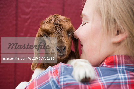 A girl cuddling a baby goat. Stock Photo - Premium Royalty-Free, Image code: 6118-07731891