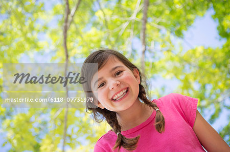 A young girl with braids wearing a pink top under a canopy of trees. Stock Photo - Premium Royalty-Free, Image code: 6118-07731979