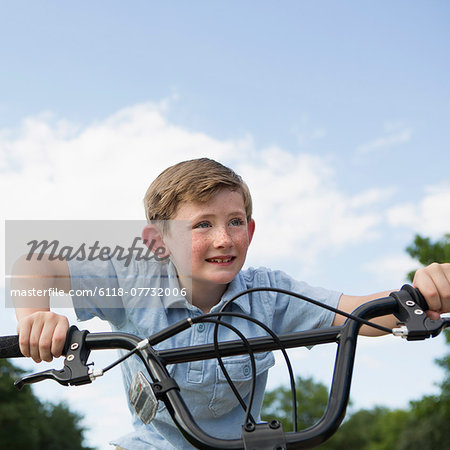 A young boy leaning over the handlebars of a bicycle. Stock Photo - Premium Royalty-Free, Image code: 6118-07732006