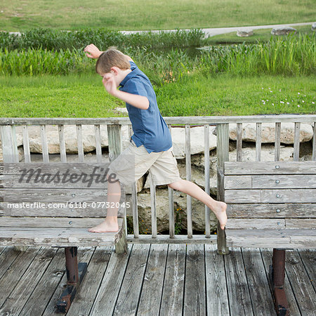 A young boy outdoors leaping from one bench to another on a jetty over water. Stock Photo - Premium Royalty-Free, Image code: 6118-07732045