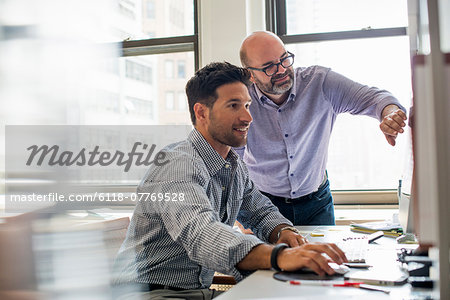 Office life. Two men in an office, using a computer screen. Stock Photo - Premium Royalty-Free, Image code: 6118-07769528
